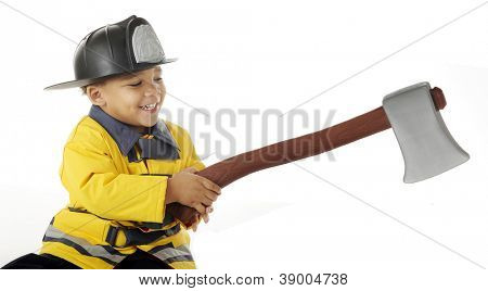 An adorable preschool fireman happily wielding a hatchet.  On a white background.