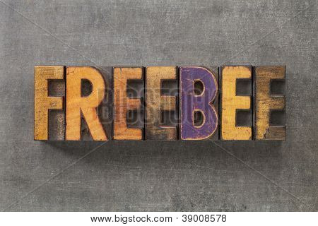 freebee word in vintage letterpress wood type blocks on grunge metal background