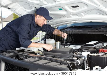 Professional car mechanic working in auto repair service.