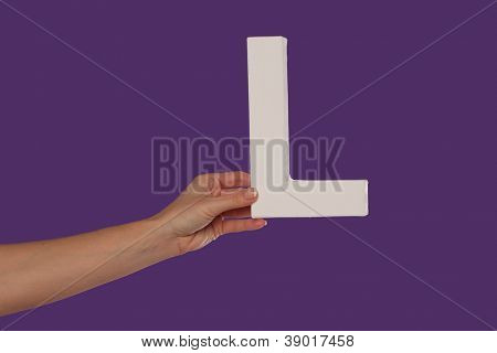 Female hand holding up the uppercase capital letter L isolated against a purple background conceptual of the alphabet, writing, literature and typeface