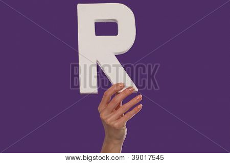 Female hand holding up the uppercase capital letter R isolated against a purple background conceptual of the alphabet, writing, literature and typeface