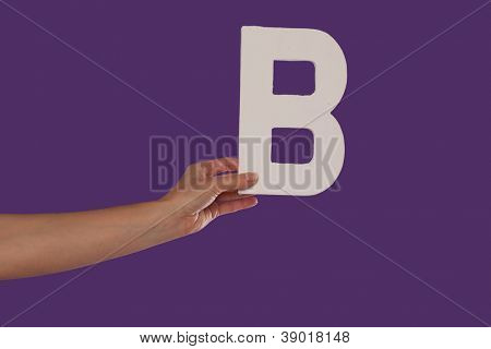 Female hand holding up the uppercase capital letter B isolated against a purple background conceptual of the alphabet, writing, literature and typeface