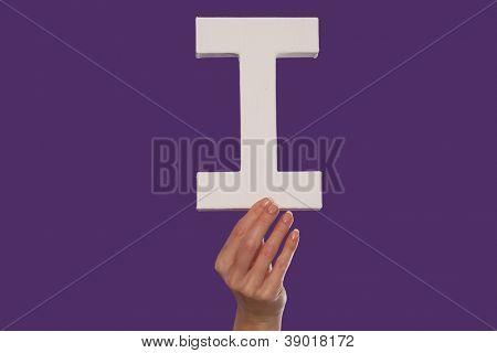 Female hand holding up the uppercase capital letter I isolated against a purple background conceptual of the alphabet, writing, literature and typeface