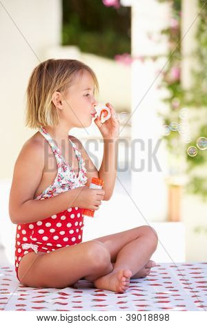 Girl Wearing Swimming Costume Blowing Bubbles