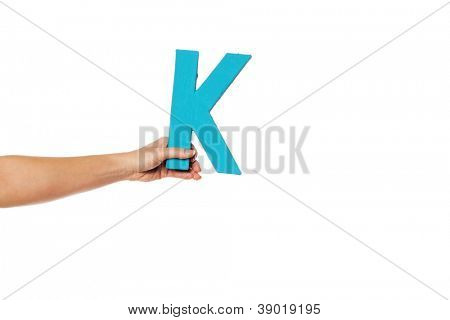 Female hand holding up the uppercase capital letter B isolated against a white background conceptual of the alphabet, writing, literature and typeface