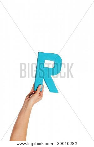 Female hand holding up the uppercase capital letter R isolated against a white background conceptual of the alphabet, writing, literature and typeface