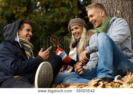 Happy young companionship sitting, talking in autumn park.