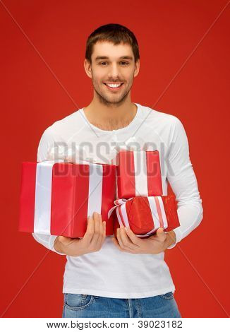 bright picture of handsome man holding many gift boxes.
