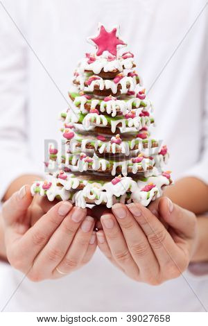 Woman and child hands holding gingerbread decorated christmas tree - shallow depth