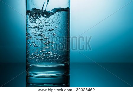 pouring water in glass closeup in blue light