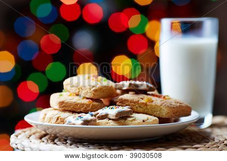 Image of tasty cookies on plate and a glass of milk