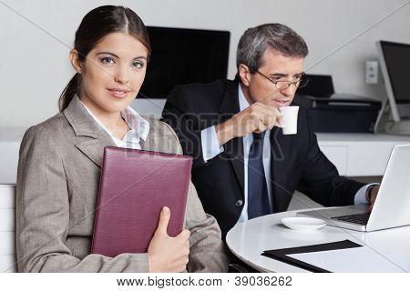 Asistente con agenda sentado junto a un empresario en la oficina