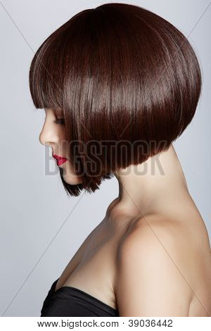 beautiful young woman wearing short bob hairstyle on studio background - focus on the eyes