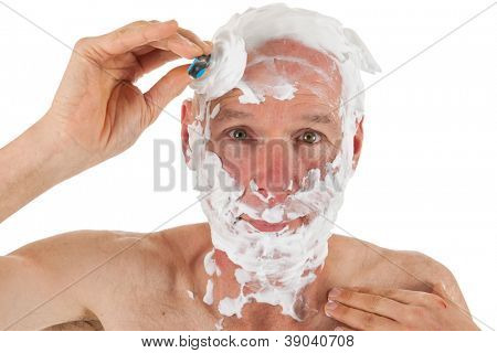 Shaving bald man with razor and foam is shaving his head