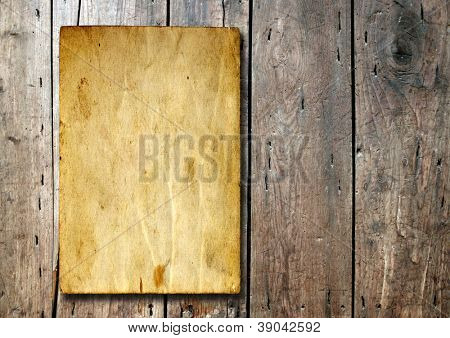 Concept or conceptual old vintage brown damaged paper texture over a wood background as a metaphor for aged,retro,wooden,dirty,textured,manuscript,antique,parchment,book,ancient,weathered or grungy