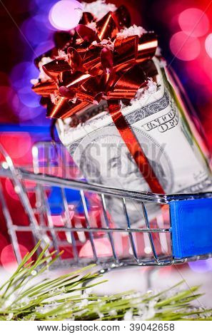 shopping cart with money against blurred lights on christmas tree