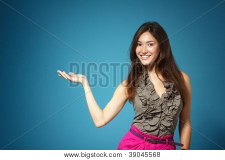 beautiful teen girl showing something with hand, over blue background