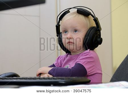 little girl in headphones on the computer learning