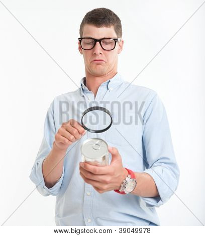 Young man inspecting a cans nutrition label with a magnifying glass