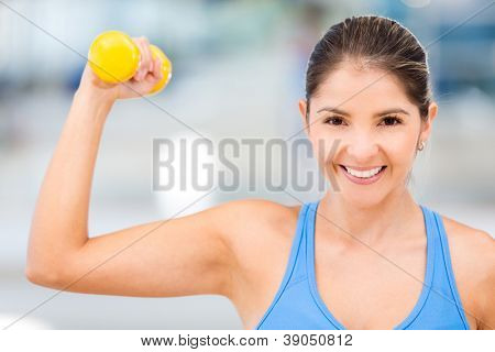 Strong woman at the gym lifting free-weights