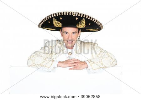 Man dressed as a mariachi with a board left blank for your message