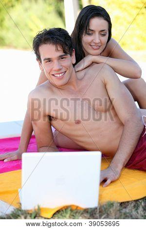 Girl looking computer over shoulder of boy