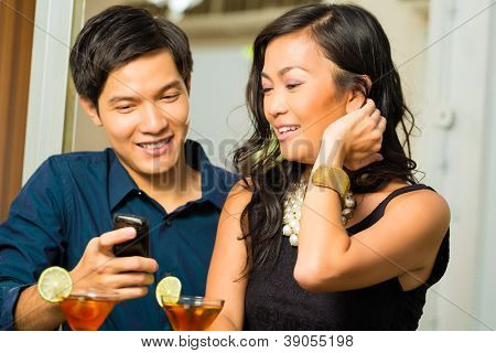 Asian man is flirting with woman in a bar while having drinks, woman is shy