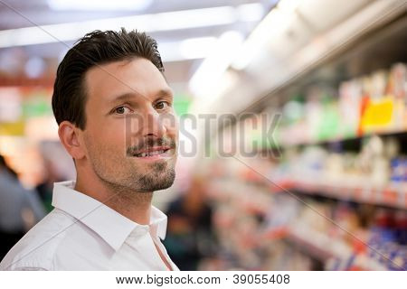 Portrait of handsome young customer smiling at supermarket