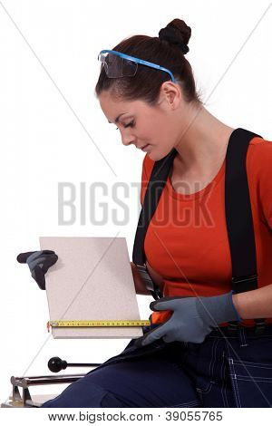 Tradeswoman measuring a tile