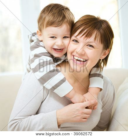 Portrait of happy son enjoying a piggyback ride on mothers back