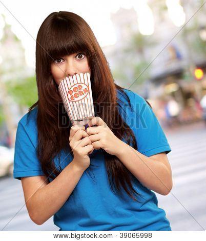 girl looking through empty popcorn packet, outdoor
