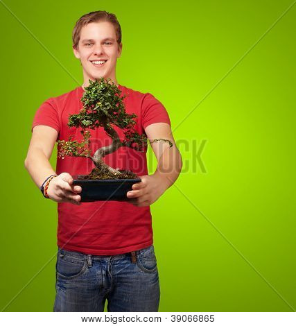 portrait of a young man holding a pot on a green background