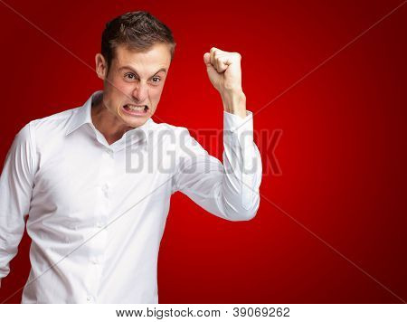 Portrait Of Angry Young Man Clenching His Fist On Red Background