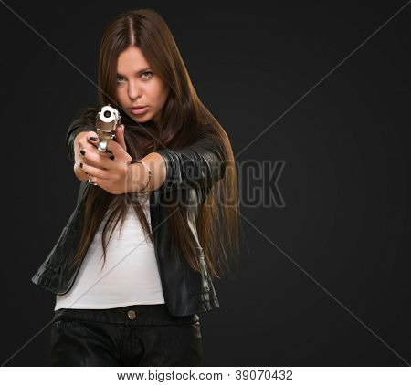 Portrait Of A Woman Holding Gun against a black background