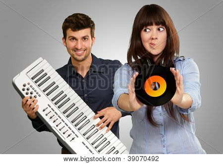 Young Girl Showing Vinyl Against Young Man Holding Piano On Gray Background