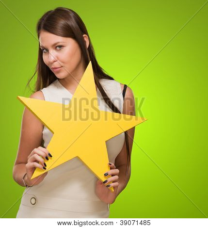 Portrait Of Young Woman Holding Yellow Star against a green background