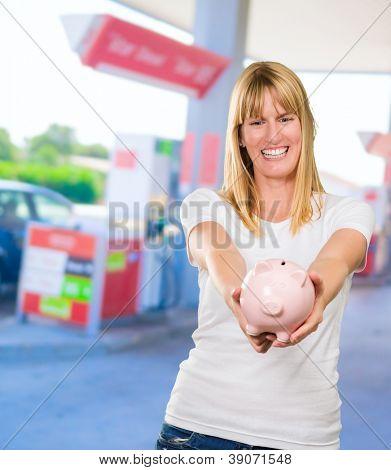 Frau Holding Sparschwein an einer Tankstelle, im freien