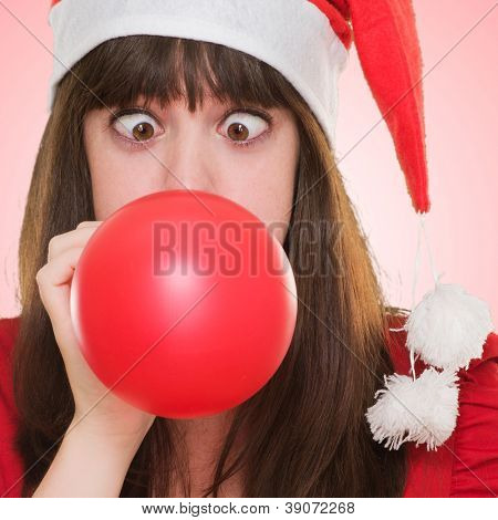 christmas woman blowing a balloon with her eyes crossed against a red background