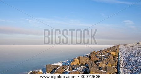 Dike along a frozen lake in winter