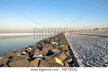 Dike along a frozen lake in winter