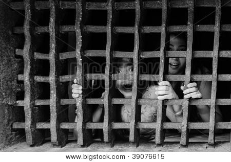 Children with afraid faces behind the bars - Black and white