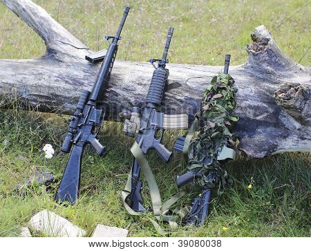military weapons for airsoft in a clearing near a wood