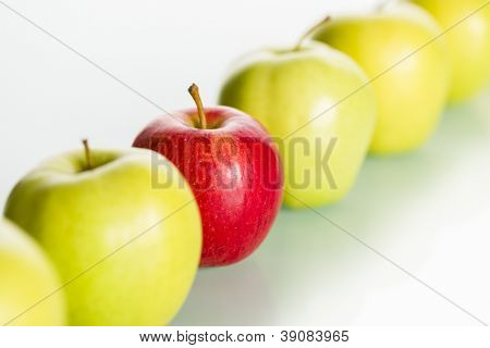 Close up of fresh red apple standing out from row of green apples, concept