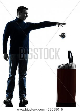 one causasian man dropping a paper in a trash bin full length in silhouette studio isolated on white background