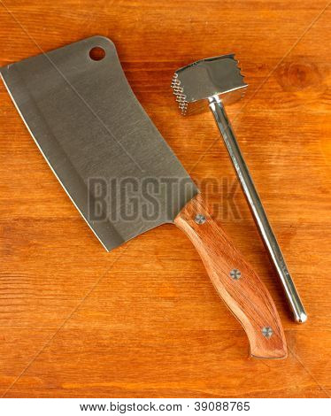meat hammer with meat hatchet on wooden background close-up