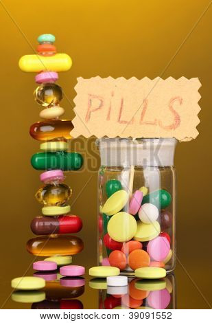 Capsules and pills hill and in receptacle on yellow background