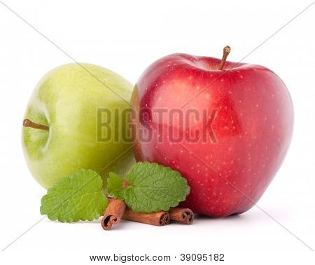 Red and green apples, cinnamon sticks and mint leaves still life isolated on white cutout