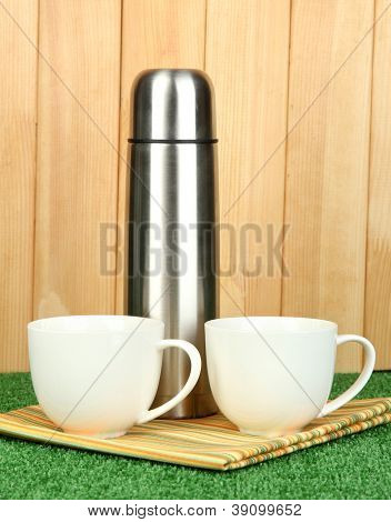 metal thermos with cups on grass on wooden background