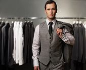 image of boutique  - Businessman in classic vest against row of suits in shop - JPG