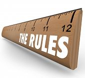 A wooden ruler with the words The Rules to represent laws, regulations, limits or guidelines meant t